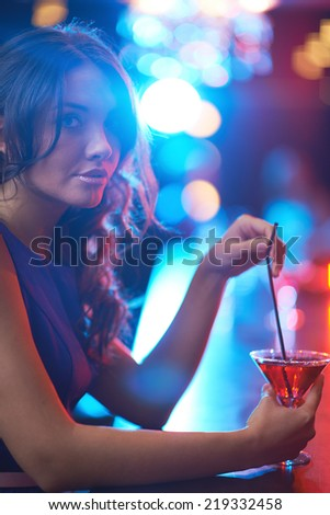 Pretty young girl with martini sitting in the bar - stock photo