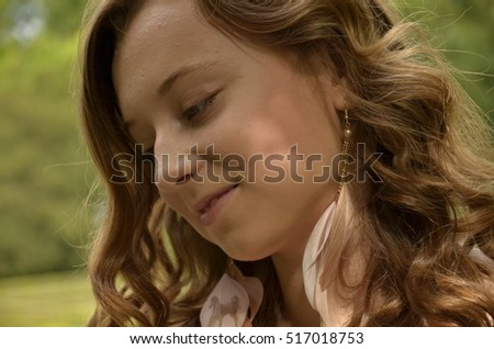 pretty young girl, woman with curly red hair pose outside in nature with smiley face in summer in sunny day