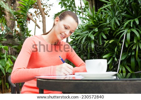 Pretty young girl writing notes - stock photo