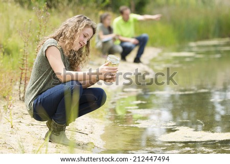 Pretty young girls having outdoor science lesson  exploring nature  - stock photo