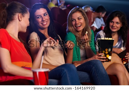 Pretty young girls sitting in auditorium of cinema, talking, smiling, eating popcorn.