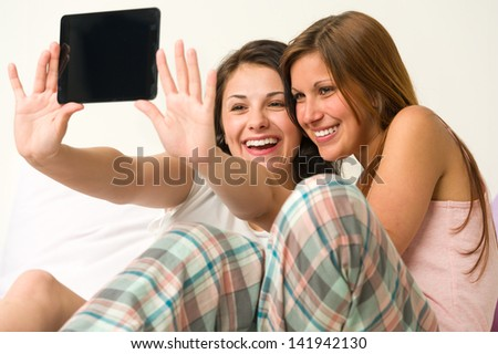 Pretty young girls taking pictures of themselves smiling - stock photo