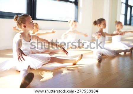 Pretty Young Girls, Wearing White Tutus, Sitting on the Floor at the Studio While Having a Training for Ballet Dance. - stock photo