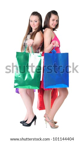Pretty young girls with colorful shopping bags standing back to back - stock photo