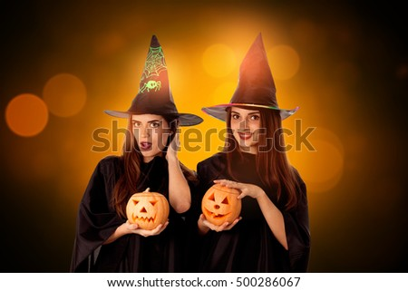 pretty young girls with pumpkins in hands in halloween style posing in studio