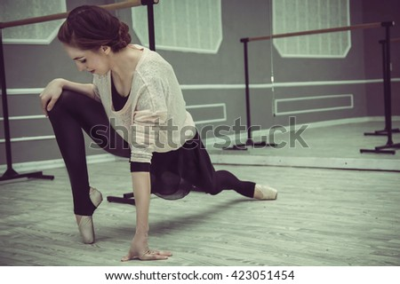 pretty young graceful ballet dancer warms up in ballet class - stock photo