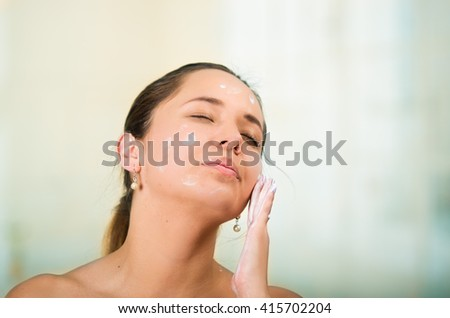 Pretty young healthy hispanic woman headshot with naked shoulders, applying cream to face using hands - stock photo