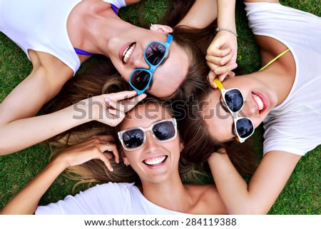 Pretty young hipster woman laying on the grass, smiling and having fun, wearing bright sunglasses and white tops. Group of friend enjoying their time out, joy, vacation time. - stock photo