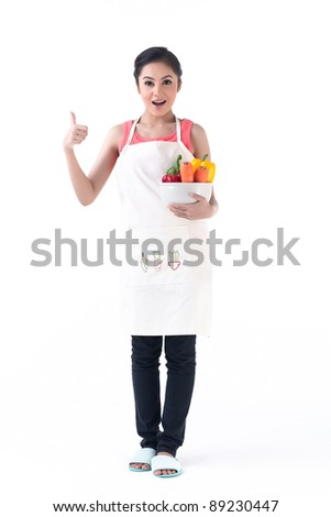 Pretty young housewife holding a bowl of vegetable and thump up - stock photo