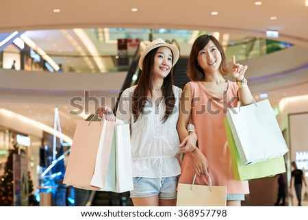 Pretty young Korean girls with many shopping bags standing in the mall