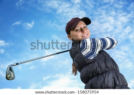 Pretty young lady golfer view from below against a blue sky - stock photo