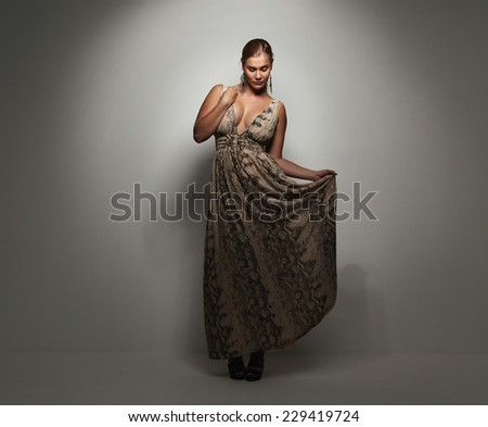 Pretty young lady in a evening dress standing on grey background. Plus size caucasian female model posing in beautiful evening gown. - stock photo
