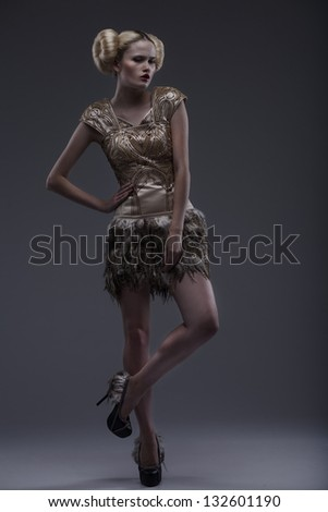 Pretty young lady in a fashion pose on dark grey background - stock photo