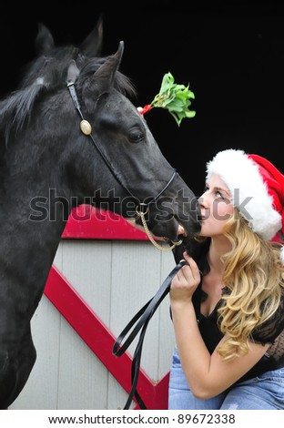 pretty young lady in a Santa hat holding a mistletoe over her black horse - stock photo