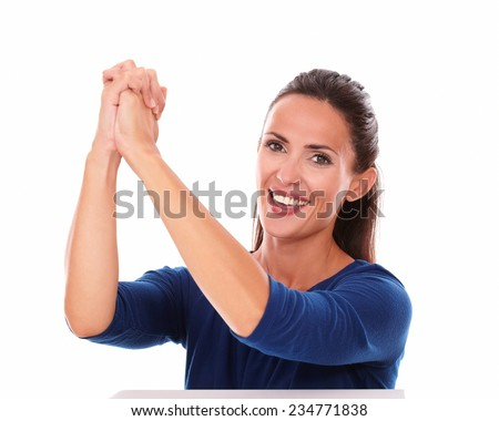 Pretty young lady in blue shirt gesturing winning while looking at you in white background - stock photo
