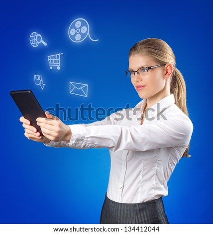 Pretty young lady looking at social media icons. Attractive blond in business style in eyeglasses holding tablet PC in her hands. - stock photo