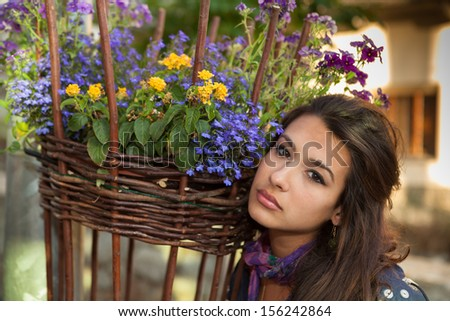 Pretty young lady next to a colorful basket of flowers. - stock photo