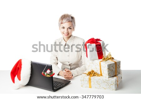 Pretty young lady sitting at desk with  laptop present boxes and winter hat over white background