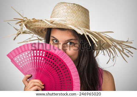 Pretty young lady with blue eyes wearing a straw hat and a pink fan - stock photo