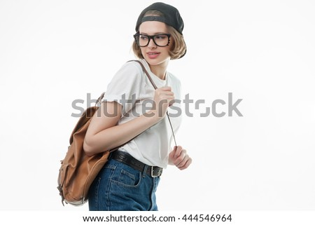 Pretty young lady with short hair posing in studio isolated on white background holding handbag and looking apart. school girl in black cap and glasses. Student girl is going to university, graduated