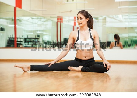 Pretty young Latin brunette doing some stretching exercises and warming up at the gym - stock photo