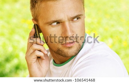 Pretty young man sitting on wooden bench and talk on mobile phone, against green of summer park.