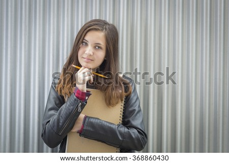 Pretty Young Melancholy Female Student With Books and Pencil Looking to the Side. - stock photo
