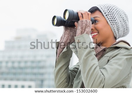 Pretty young model in winter clothes watching the city with binoculars outside on a cloudy day