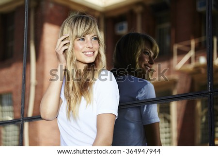 Pretty young model looking away against glass - stock photo