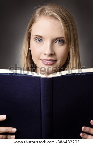 Pretty young model who is reading, holding an open blue book infront of her,  keeping the book near her face whole expressing positivity.