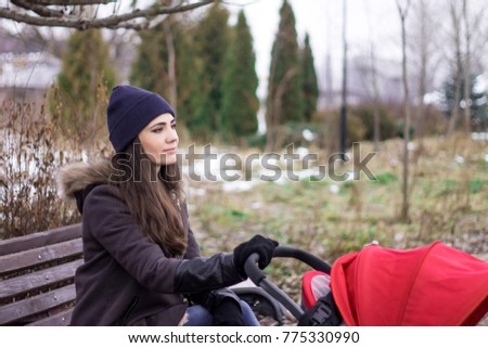 Pretty young mom out at a local park with baby asleep in a stroller, winter time, cloudy cold weather