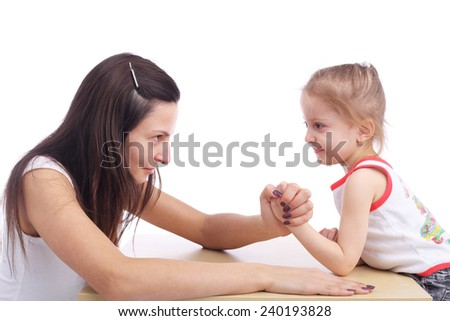 pretty young mother arm wrestling with her cute little daughter - stock photo