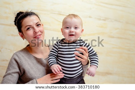 Pretty young mother holding her happy healthy baby son in her arms as he happily grins at the camera, with copy space - stock photo