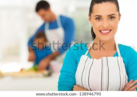 pretty young mother in front of family in kitchen - stock photo