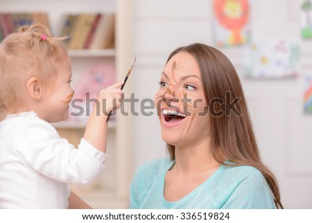 Pretty young mother is spending time with her daughter. The girl is applying the paint on the face of woman. She is holding a brush with threats. They are smiling - stock photo