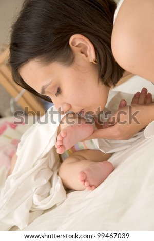 Pretty young mother kissing the tiny feet of her newborn baby who is sleeping in bed