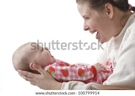 Pretty young mother laughs delightedly at her happy smiling baby. They are face to face. Mother wears white sweater, baby has strawberry print sleepers. Isolated on white, horizontal with copy space.