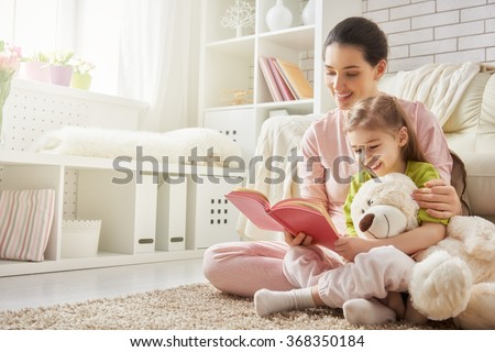 pretty young mother reading a book to her daughter - stock photo