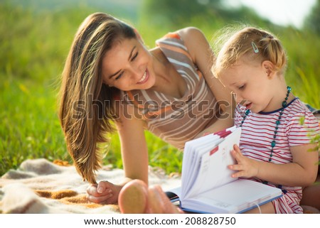 Pretty young mother reading book to her little daughter at green meadow - stock photo
