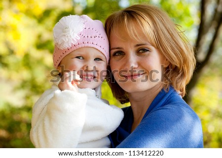 Pretty young mother with her little daughter in the cap - stock photo