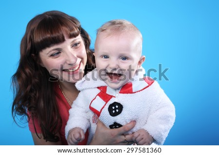 pretty young mother with the cute little baby on the blue background - stock photo