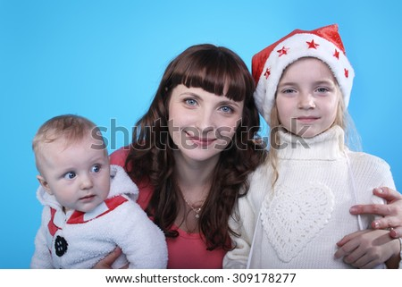 pretty young mother with the cute little children on the blue background