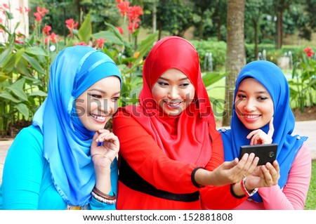 Pretty young Muslim girl taking picture with smart phone