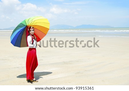 Pretty young Muslim woman walking at beach. - stock photo