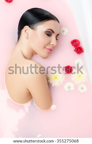 Pretty young naked woman is relieving stress in bath with flowers. She is lying with cute smile. Her eyes are closed with pleasure - stock photo