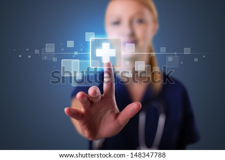 Pretty young nurse pressing modern medical type of buttons - stock photo