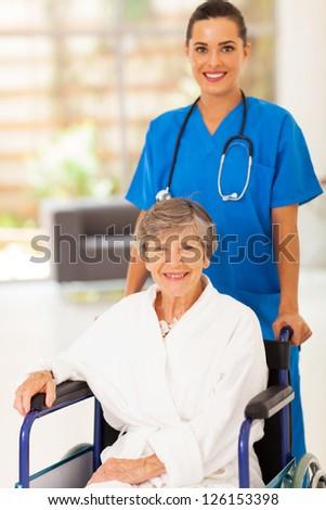 pretty young nurse pushing senior woman on wheelchair - stock photo