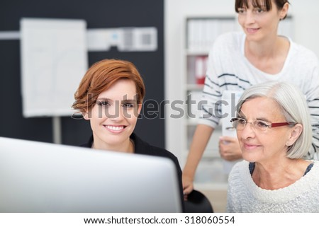 Pretty Young Office Woman Sitting at her Desk with her Two Female Colleagues Next to her Looking at her Computer Screen. - stock photo