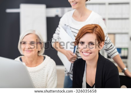 Pretty Young Office Woman Smiling at the Camera While Doing a Group Task with Other Two Colleagues. - stock photo