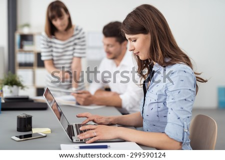 Pretty Young Office Woman Typing on her Laptop Computer on the Table Inside the Boardroom - stock photo